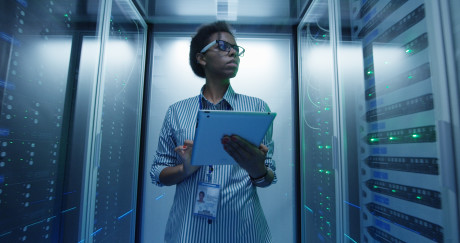 Adult African American woman using tablet while walking among server racks in data center corridor and doing diagnostics